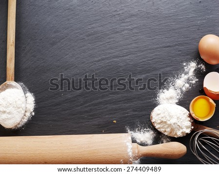 Dough preparation. Baking ingredients: egg and flour on black board. - stock photo