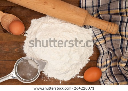 Dough preparation. Baking ingredients: eggs and flour, sieve and rolling pin on wooden background. Top view - stock photo