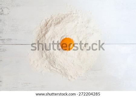 Dough raw ingredients on white table background. Egg yolk and flour - stock photo