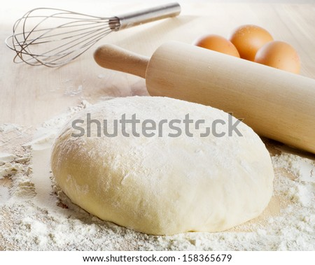 Dough with eggs  on wooden table. Selective focus - stock photo