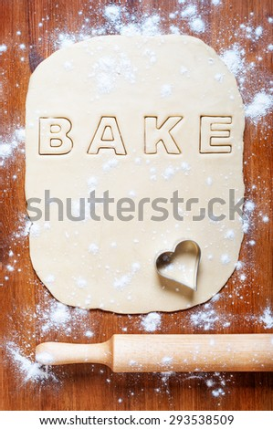 Dough with letters and rolling pin on the wooden table. Kitchen background