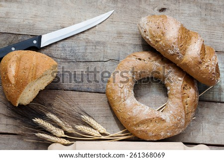 doughnut rye bread and cereal french bread over wood with knife - stock photo