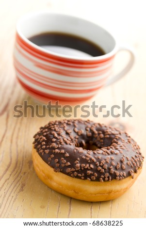 doughnut with black coffee on wooden table - stock photo