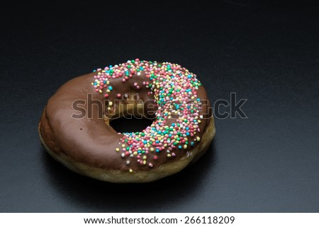 doughnut with color sprinkles on black table - stock photo