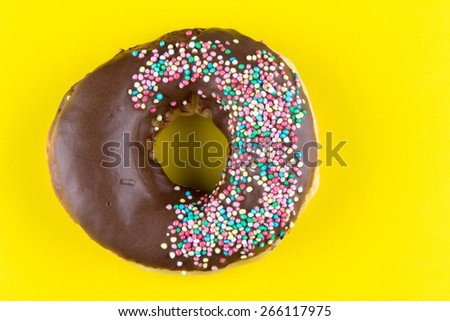 doughnut with color sprinkles on yellow table - stock photo