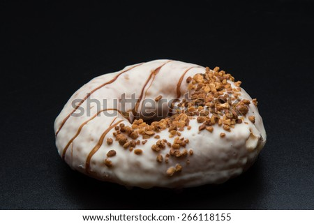 doughnut with nuts on black table - stock photo