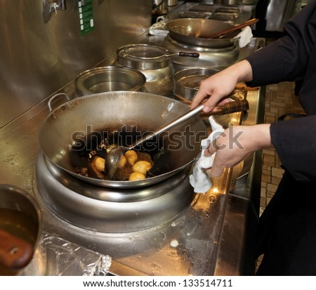 Doughnuts being fried in oil in wok pan, asian restaurant