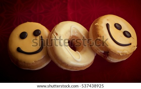 Doughnuts with glazed cream and smiley choco decoration