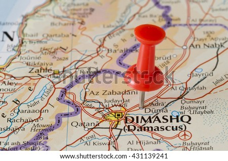 Douma (Duma) marked on map with red pushpin. Selective focus on the word Duma and the pushpin. Pin is in an angle. Midground is sharp while foreground and background is blurry. - stock photo