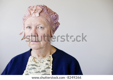 Dour senior woman in the studio wearing a vintage hat and lace. - stock photo