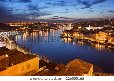 Douro river flows through a beautiful city of Porto at night in Portugal. - stock photo