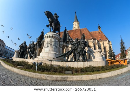 doves flying over the statue of mathias rex in unirii square, cluj-napoca. fisheye shot - stock photo