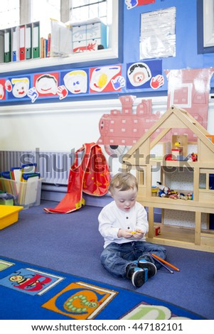 Down Syndrome boy playing with colouring pencils in his nursery classroom. - stock photo