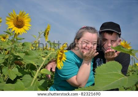 down syndrome couple with sunflower - stock photo