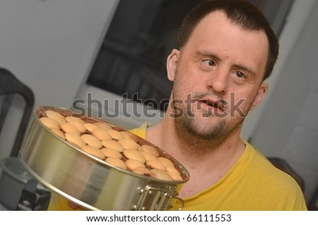 down syndrome man in his kitchen - stock photo