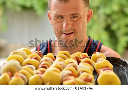 down syndrome man with barbecue - stock photo