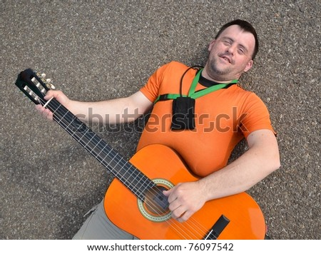 down syndrome man with guitar - stock photo