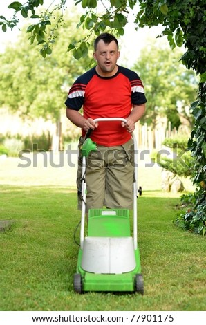 down syndrome man with lawn mower - stock photo