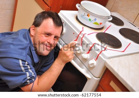 down syndrome man with stove - stock photo