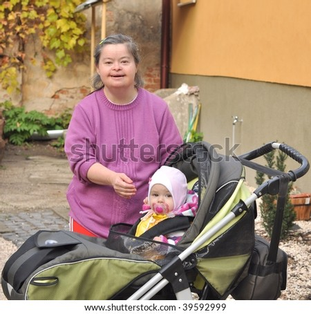 down syndrome woman with baby in stroller - stock photo