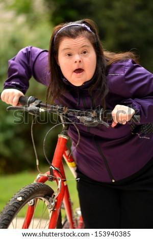 Down syndrome woman with bicycle - stock photo