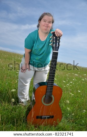 down syndrome woman with guitare - stock photo