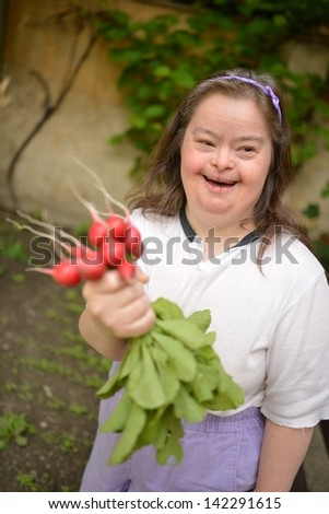 down syndrome woman with radish - stock photo