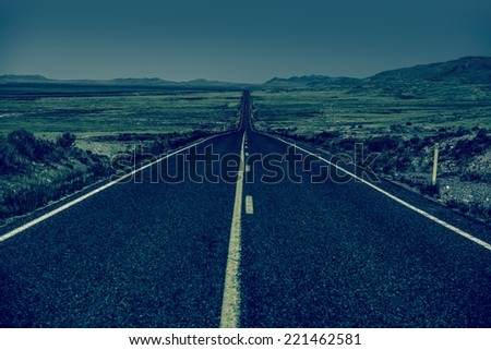 Down the Road. Straight Desert Highway in Bluish Color Grading. Straight Road to Nowhere. - stock photo