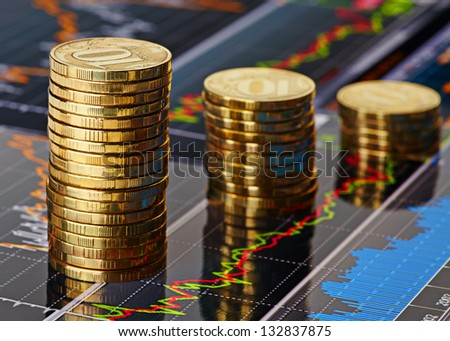 Down trend stacks of coins and financial chart as the background - stock photo