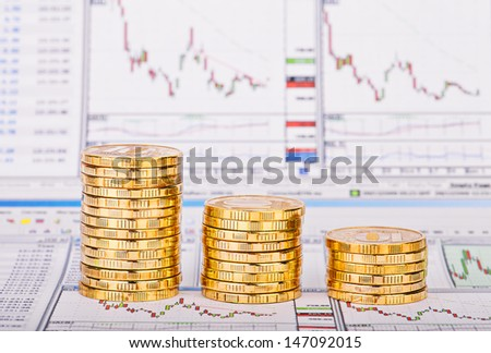 Down trend stacks of golden coins and financial chart as the background. Selective focus - stock photo