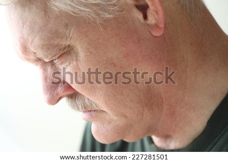 Downcast senior man with an expression of sadness, depression or grief - stock photo