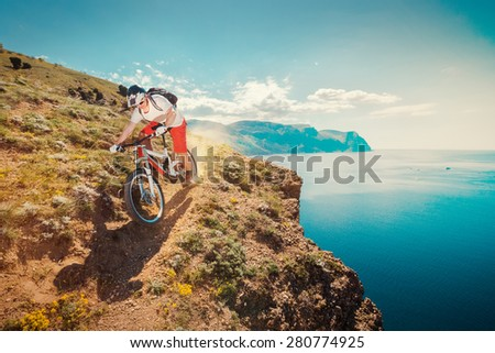 Downhill bike. Down from the mountain on a mountain bicycle. Extreme sport. Man riding outdoors lifestyle trail. - stock photo