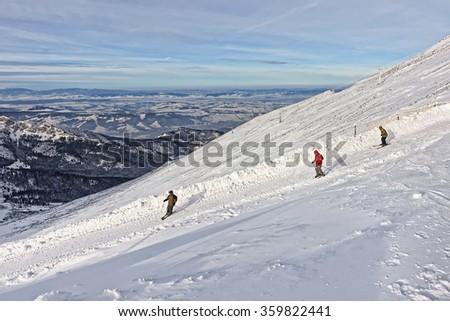 Downhill Skiers on Kasprowy Wierch in Zakopane in Tatras in winter. Zakopane is a town in Poland in Tatra Mountains. Kasprowy Wierch is a mountain in Zakopane and the most popular ski area in Poland - stock photo