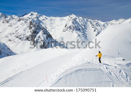 Downhills with skiers are photographed against the snow-covered mountain range in the spring Pyrenees. - stock photo