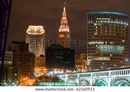 Downtown buildings of Cleveland, Ohio, lit up at night under a glowering sky - stock photo