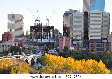 downtown Calgary, Alberta, Canada in the evening. New Bow Tower being built by EnCana can be seen beyond the bridge. - stock photo