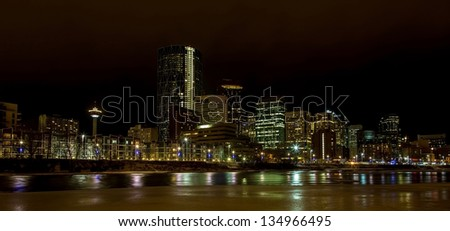 Downtown Calgary at night in winter with Bow river - stock photo