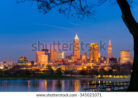 Downtown Cleveland, Ohio, glows in setting sunlight as the full moon prepares to rise under the pink clouds at center left - stock photo