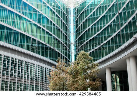 Downtown corporate business district architecture: glass reflective office buildings against blue sky with clouds and sun light - stock photo