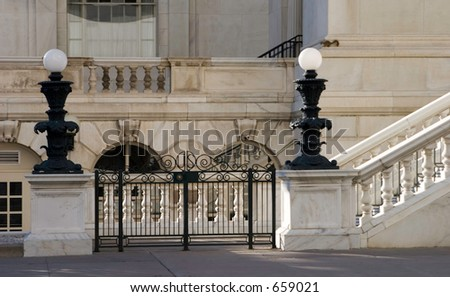 Downtown Denver court building with stone balustrade and locked iron fence keeping people out.  A lone squirrel encroaches the area, on the ledge, slightly out of focus. - stock photo