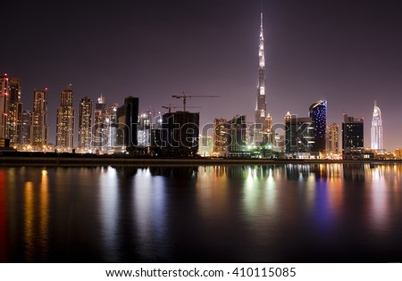 Downtown dubai skyline or cityscape in the night with burj khalifa and its reflection in the water. United arab emirates