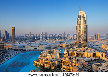 DOWNTOWN DUBAI, UAE - MAY 7 - The Dubai Fountain is set on the 30-acre manmade Burj Khalifa Lake. 63-storey, 302.2 m Address Hotel is visible on the right. Picture taken on May 7, 2010. - stock photo