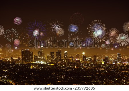 Downtown Los angeles cityscape glowing in the night with flashing fireworks celebrating New Year's Eve. - stock photo
