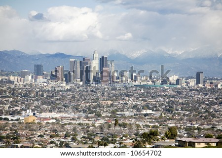 Downtown Los Angeles skyline with smaller buildings and homes in the forground and mountains in the background.