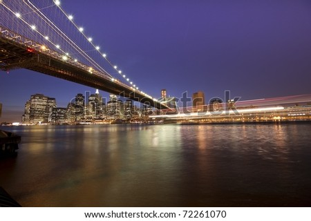 Downtown Manhattan and Brooklyn bridge with a passing boat giving the impression of movement