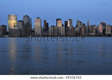Downtown Manhattan buildings reflecting the pink of the sky at sundown