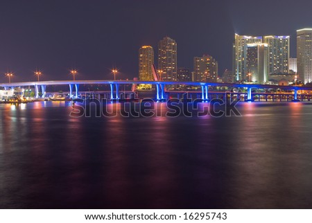 Downtown Miami Bayfront Skyline at Night, Showing Business, Residential and Entertainment Districts and Illuminated Bridge from Mainland to Port - stock photo