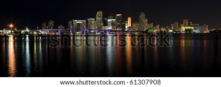 Downtown Miami Skyline Panorama with Biscayne Bay and reflecting lights on the bay. - stock photo