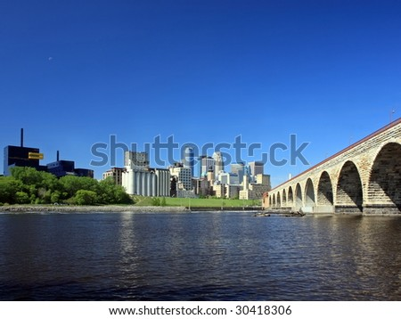 Downtown Minneapolis and Stone Arch bridge over Mississippi river - stock photo