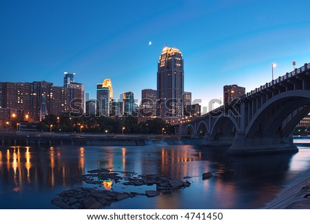 Downtown Minneapolis Minnesota & Partial Moon - St Anthony Falls and lock & dam in foreground - stock photo